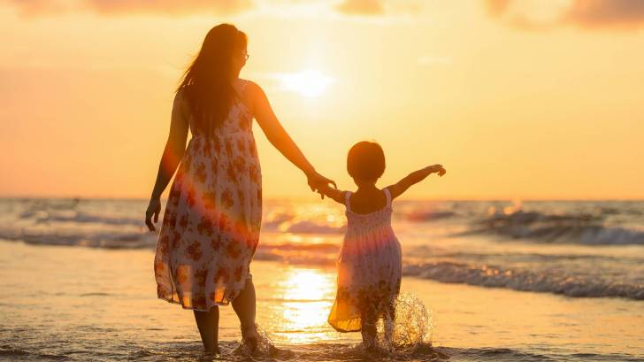 mom and young daughter walking on beach at sunset