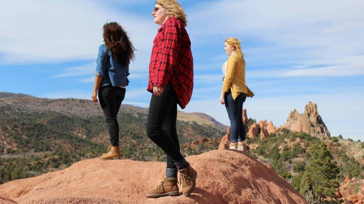 three young women on mountain top looking out at blue sky