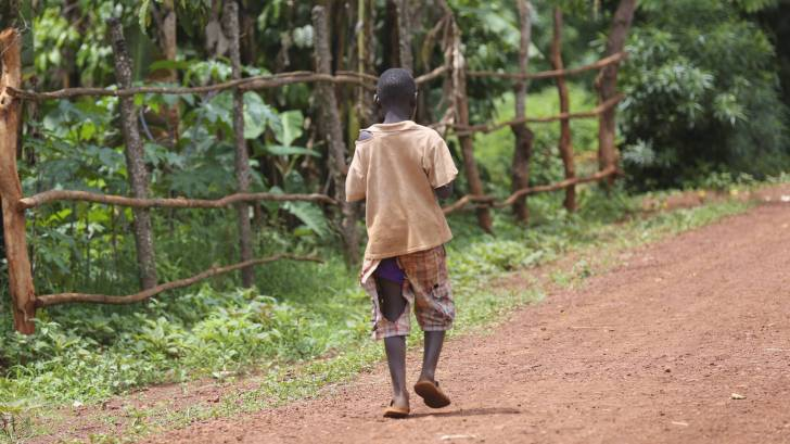 african boy walking down the dirt road