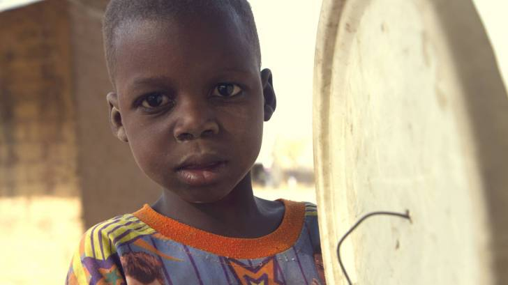 young nigerian boy holding a drum