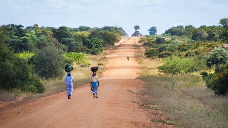african women walking to get water on dusty road