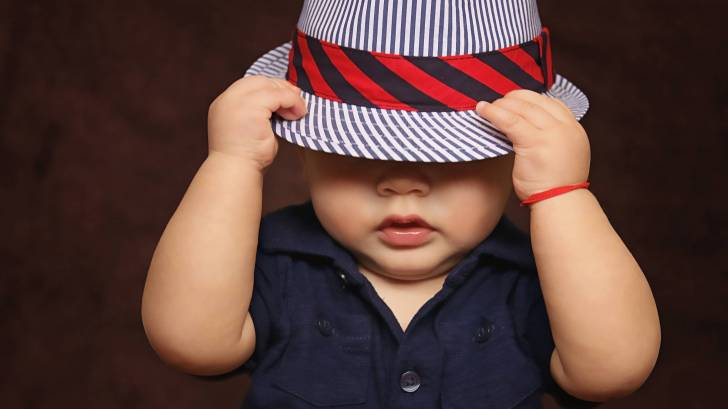 young toddler boy with hat over his eyes