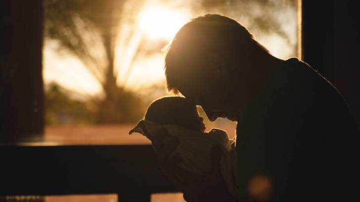 father holding new born infant with the sun setting in the background