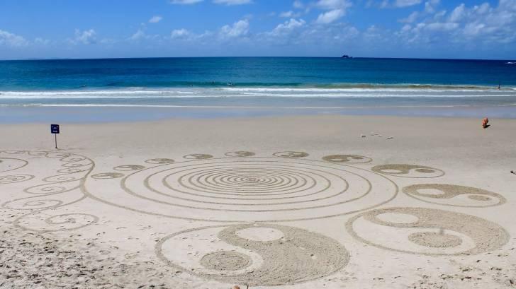 yin and ynag artwork on a beach