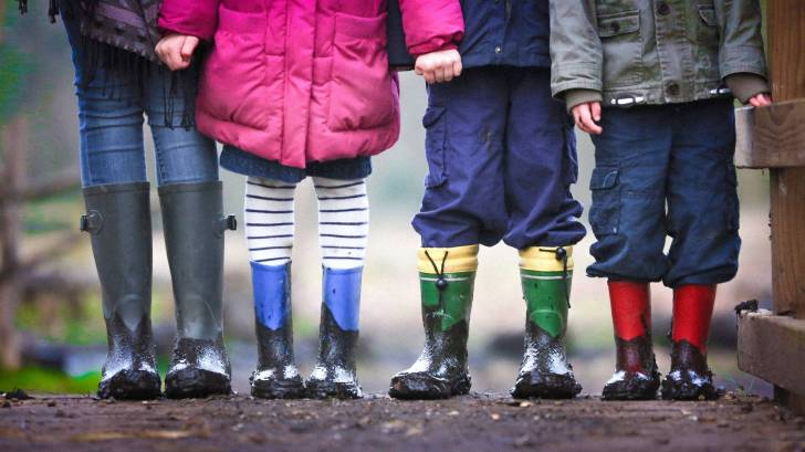 young children holding hands with rain boots on and coats