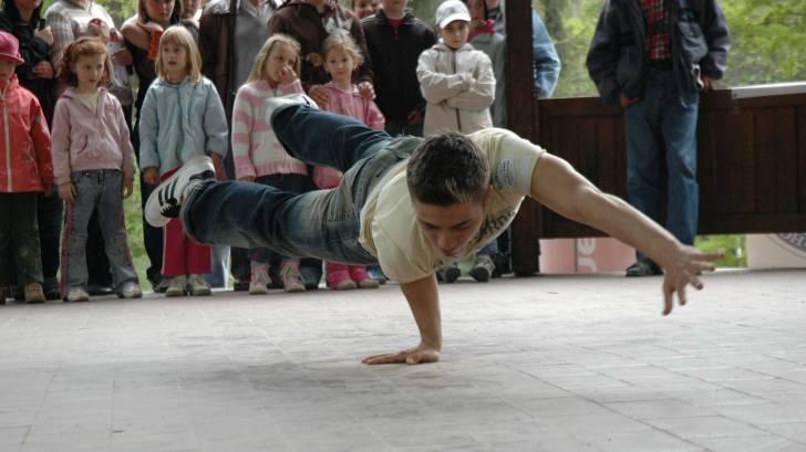 young man break dancing in front of group of teens