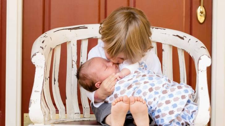 older sibling kissing new born baby