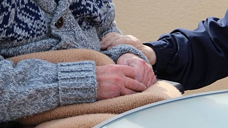 older person in nursing home being taken care