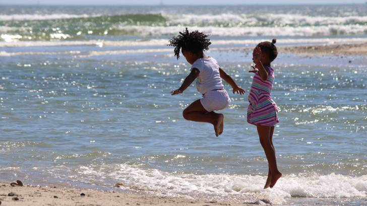 children jumping high in the ocean