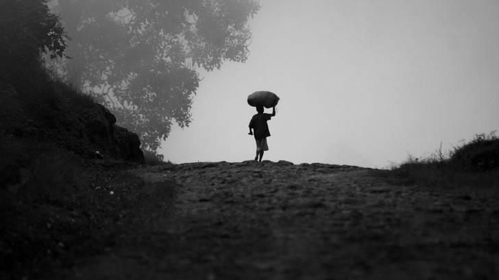 child in uganda walkng with food on his head thru the mist