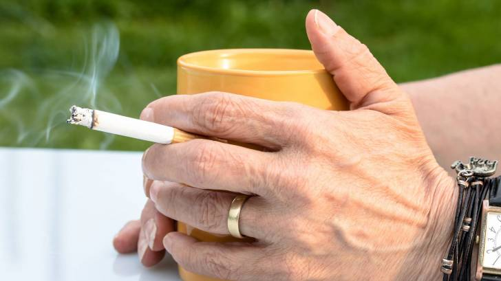 person smoking a cig with a cup of coffee