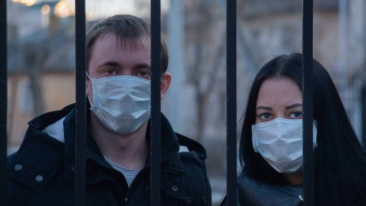 two people with masks on their faces looking through a fence