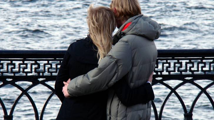 young couple hugging on a bridge
