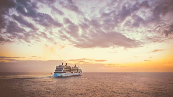 cruise ship on the ocean sun setting behind