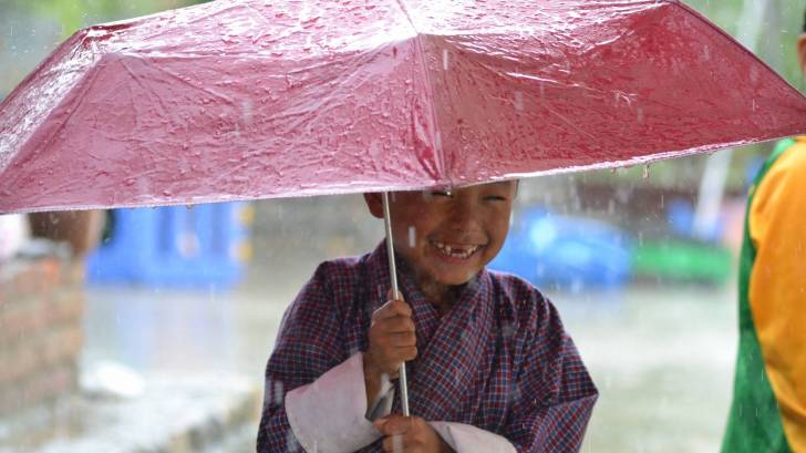 cute little boy holding umbrella in the rain