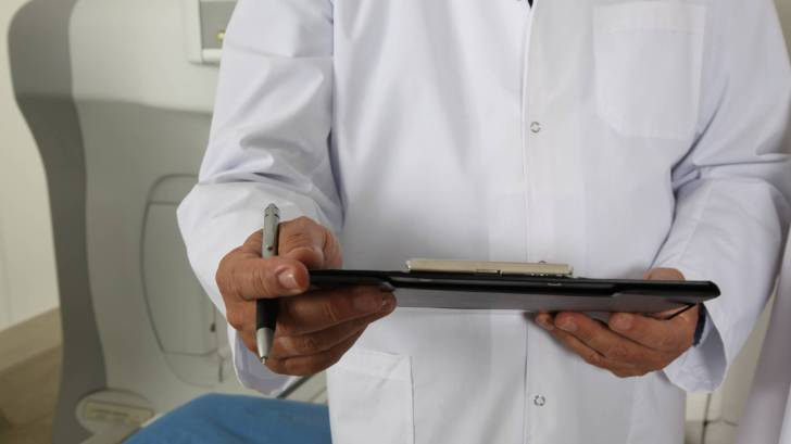 doctor with a clip board checking on a patient