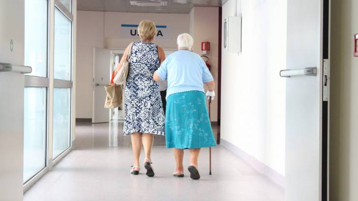 older woman being helped to walk