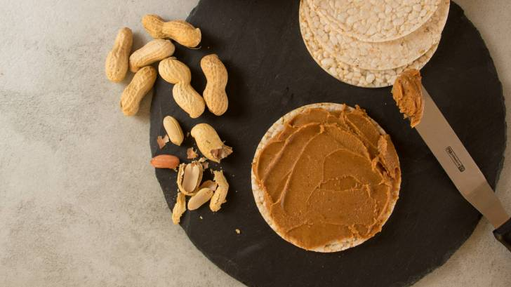 peanuts and peanut butter on rice cakes
