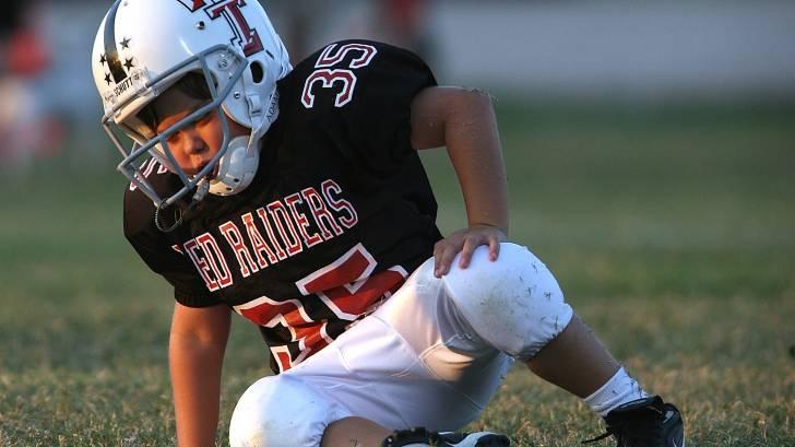 little boy in a football uniform
