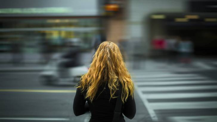 young woman watching the world go by fast in a blur