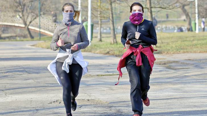 women running in a park, with masks and separate, no others around them