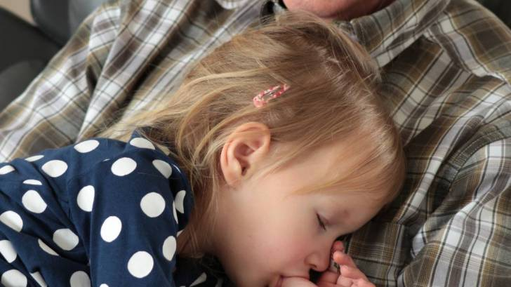 grandfather holding sleeping grand daughter