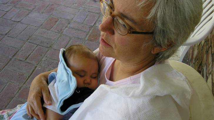 grandma rocking a new born baby