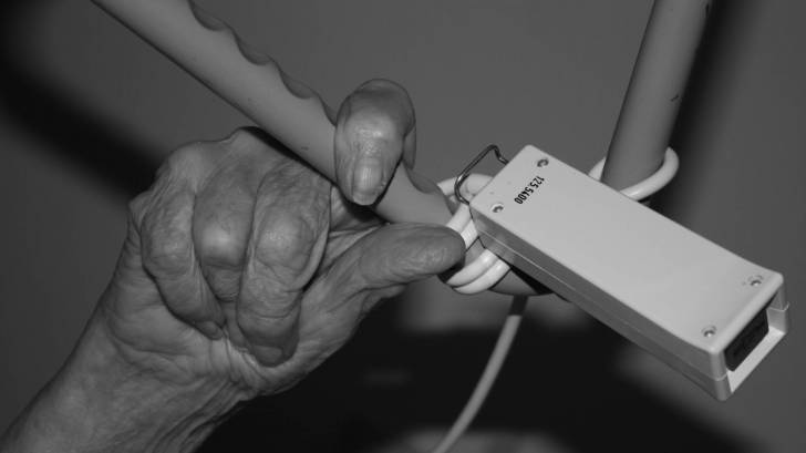 old person's hand holding on a hospital bed rail