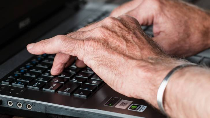 old hands typing on key board