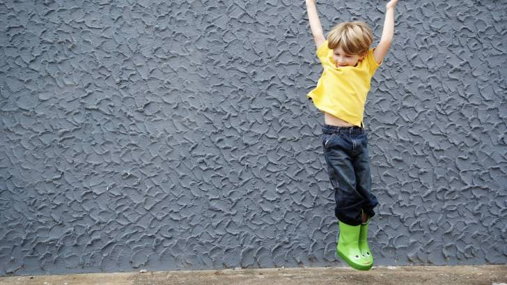 happy boy jumping in green boots