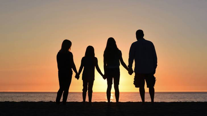 family on beach at sunset holding hands