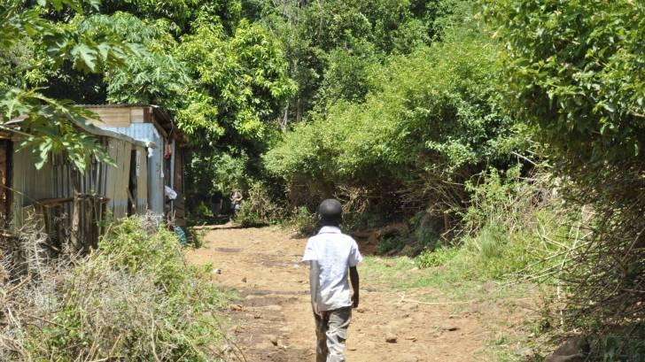 young boy walkng through a village
