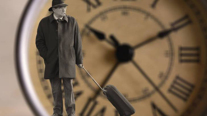 man standing by a clock