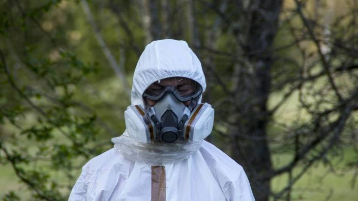 Man in bio hazard wuit and gas mask