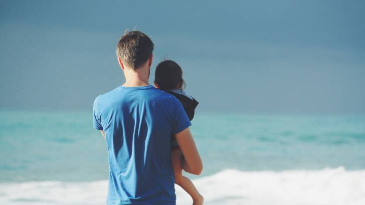 happy dad with child looking at the ocean surf