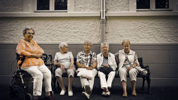 older women sitting on a bench at a retirment home