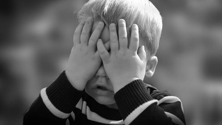 toddler covering his eyes with his hands
