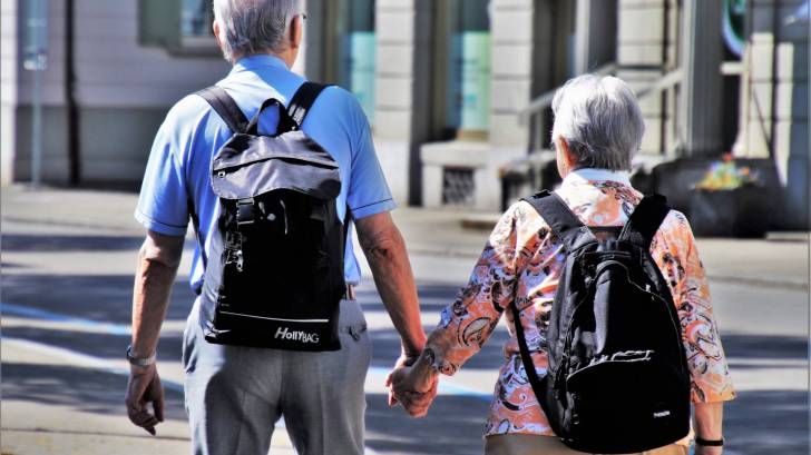 senior man and women walking holding hands