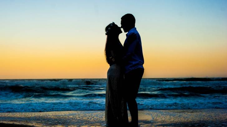 pregnant husband and wife on a beach at sunset in a silhouette