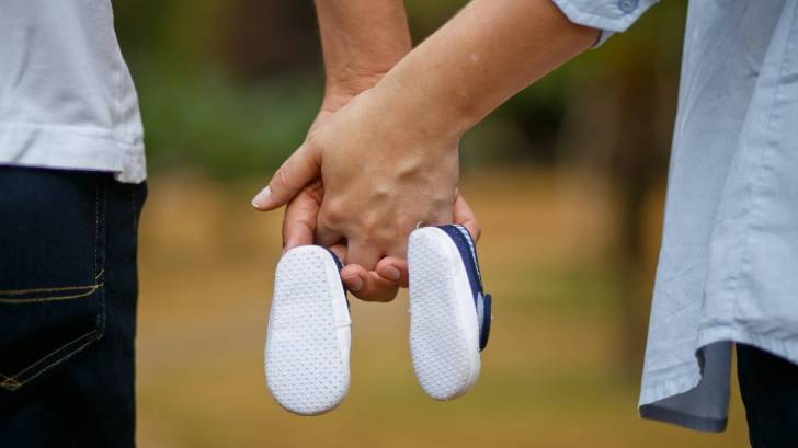 man and wife holding baby shoes