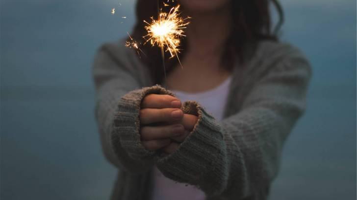 woman holding a sparkler celebrating