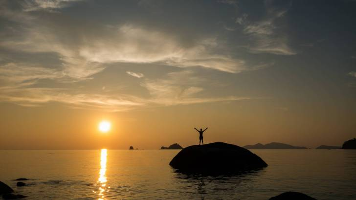 sunset person on small island with hands up