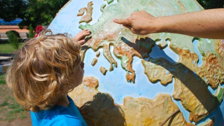 child looking at a world globe
