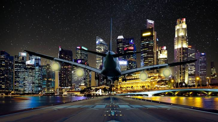 jet landing at night city lights in the background