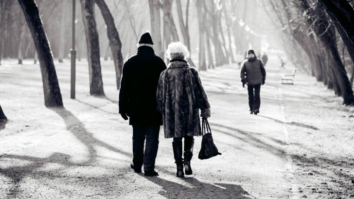 senior couple walking on a cold winter day thru a park