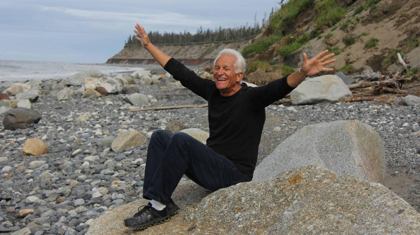 baby boomer on rocks near ocean