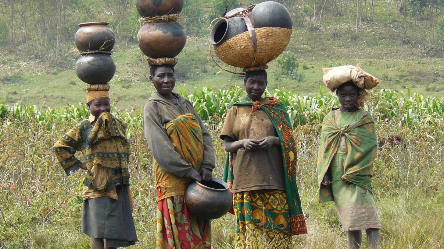 african women gathering water in pots on their heads