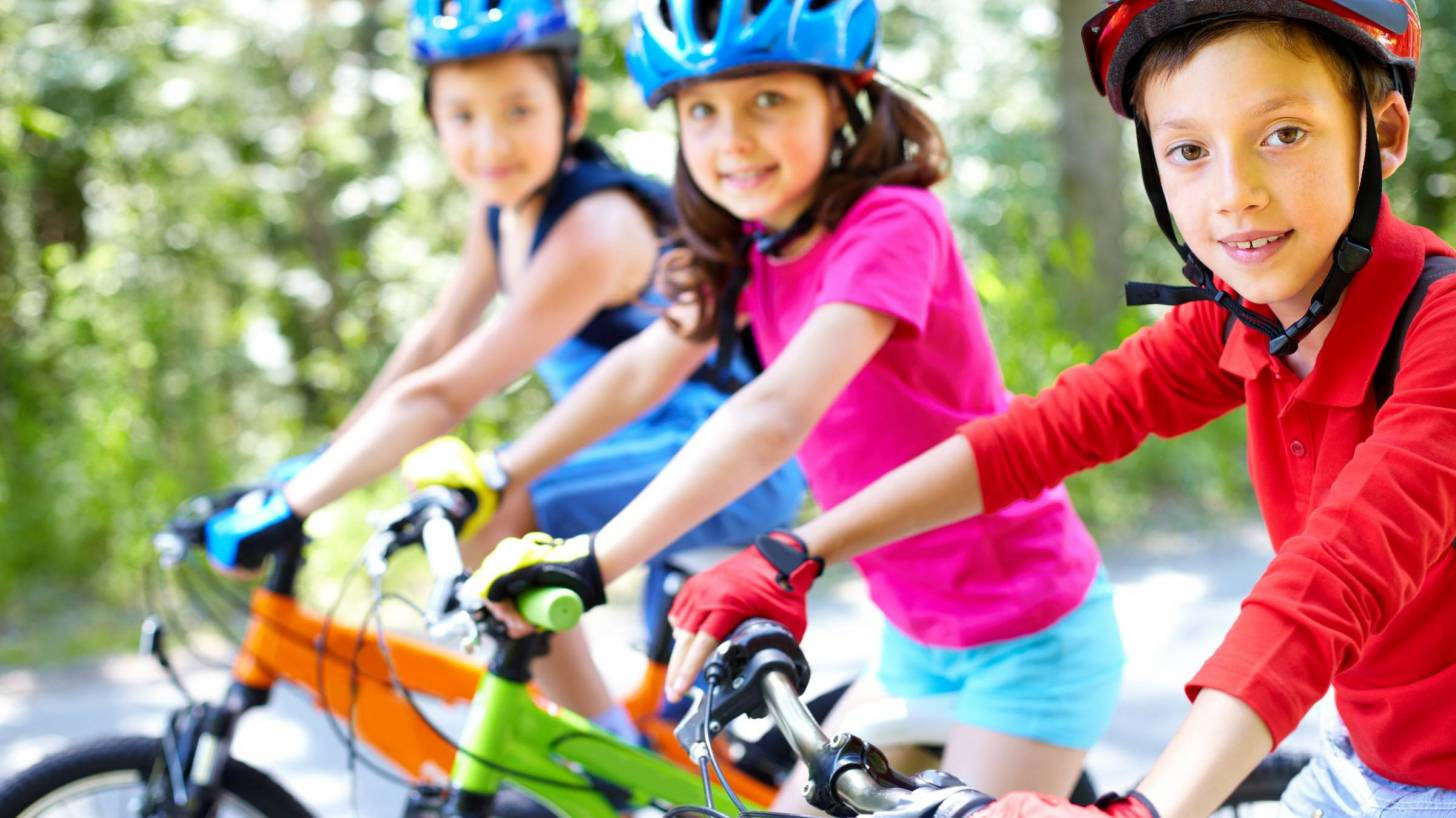 children riding bikes with helmets on