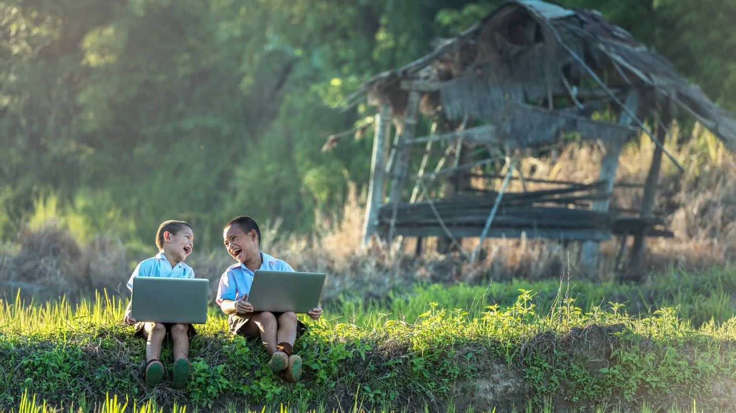 two children laughing working on their lap tops outside