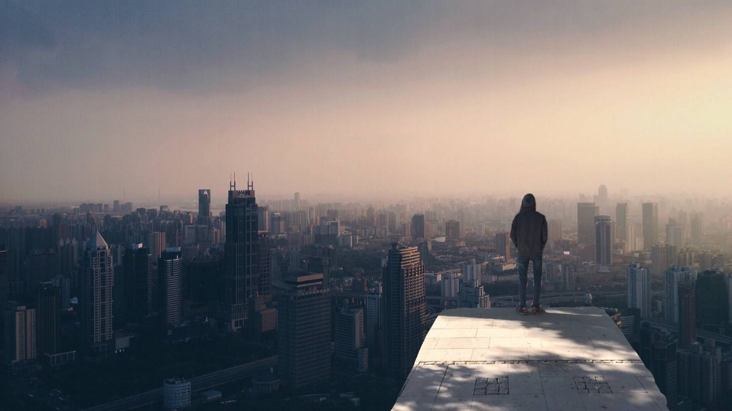 man standing on the edge of a building looking over the city